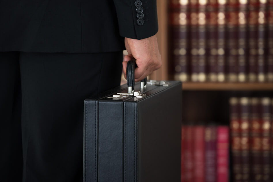 business litigation attorney carrying briefcase in office